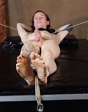 Mistress Alison Tyler has her slave's balls tied down with rope, all the better for toying with his cock.
